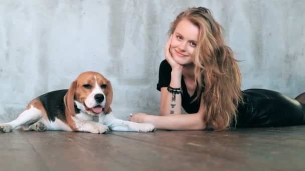 Beautiful young woman with dog playing at home