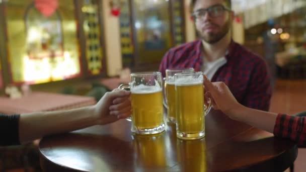 Csoport vagy a cég a meg - fiatal fiúk és lányok gazdaság pohár sört, néz foci, nevetett, és mosolygott