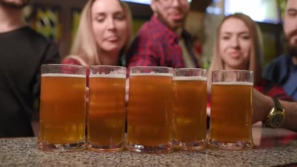 Freunde - junge Burschen und Mädchen trinken Bier, reden und lächeln an der Bar