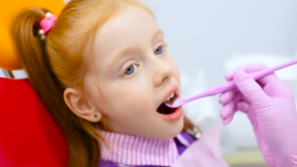 dětský zubař zkoumá zuby a ústa roztomilý zrzavá holčička v zubařském křesle žluto červená.