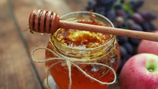med ve sklenici krásnou, dřevěnou lžící vřeteno, hrozny a jablka