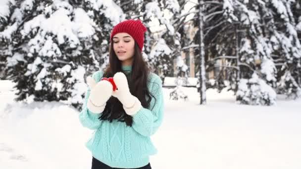 Mladá hezká dívka v modrém svetru a palčáky na pozadí zasněžených stromů držící červené srdce a usmívá se