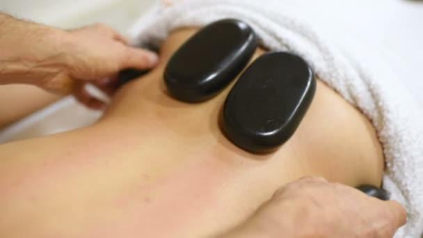 Frau Entspannung im Wellness-Salon mit heißen Steinen. Körpermassage