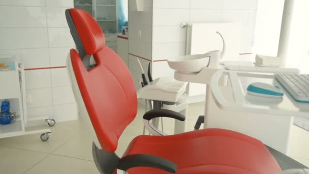 červené zubní křeslo v pozadí lékařských přístrojů