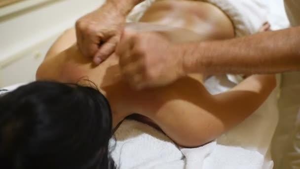 muž masér dělá masáž zad pro mladou ženu