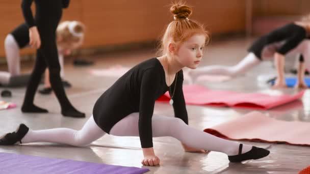 vörös hajú kislány balerina, nyújtás, és ezzel gyakorlatok, balett iskolában