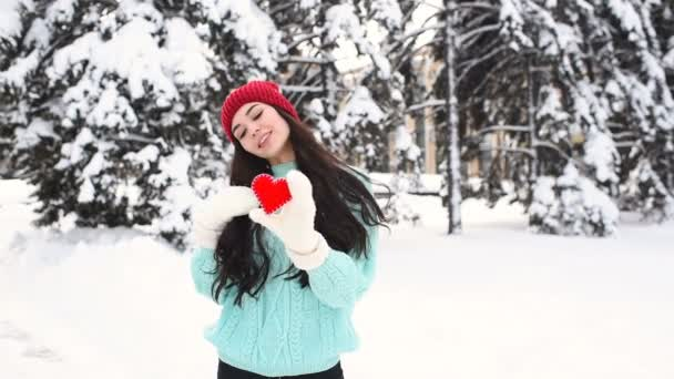 junges hübsches Mädchen in warmem blauen Pullover und Fäustlingen auf dem Hintergrund schneebedeckter Bäume, die ein rotes Herz tragen und lächeln