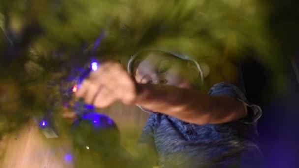 chlapec pod vánoční stromeček a pověsit vánoční ozdoby