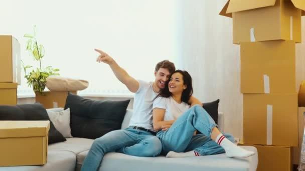 Mladý pár se stěhuje do nového bytu. Krásný pár sedí spolu na pohovce a baví se. Chlápek ukazuje dopředu. Kamera se pohybuje dozadu. Plánování apatmentů a nábytku.