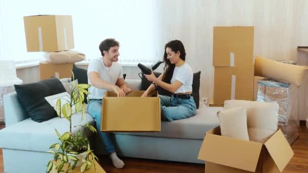 Junges Paar zieht in Wohnung. Die Leute sitzen zusammen auf dem Sofa und packen Kartons mit verschiedenen Sachen aus. Gestell, Fön und Kiste mit Geschirr herausnehmen. Gemeinsam Spaß haben.