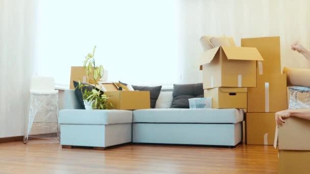 Junges Paar bezieht neue Wohnung Lustiges Video von Kerl, der in Karton sitzt. Junge Frau schiebt diese Kiste mit Mann nach vorne. Gemeinsam Spaß beim Umzug.