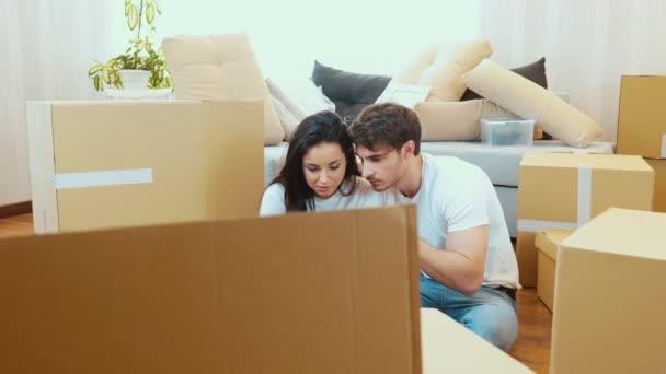 Junges Paar bezieht neue Wohnung Kamera bewegt sich aus der Box. Mann und Frau sitzen auf dem Boden und nutzen Smartphones. Suche nach Informationen. Umsiedlungszeit und -prozess.