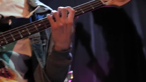 Felismerhetetlen zenész basszusgitározik a koncert színpadán fénysugarakban