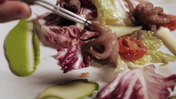 Dávám mořské jídlo na talíř s omáčkou, salátem a nakládanými rajčaty. Closeup