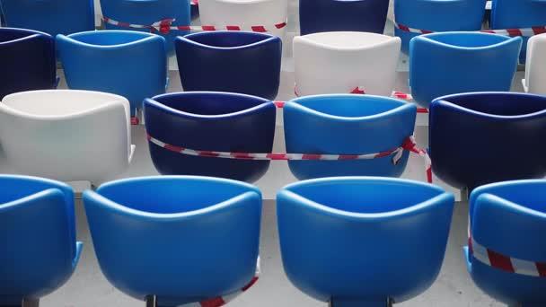 Üres székek egy biztonsági szalaggal a stadionban. Társadalmi távolság. VIZSGÁLAT