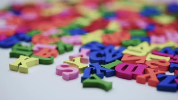 Písmena na tabulce, spinning barevná písmena na bílém stole. Koncepce studia abecedy.