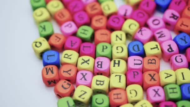 Letters on the table, spinning colored letters on a white table. The concept of studying the alphabet.