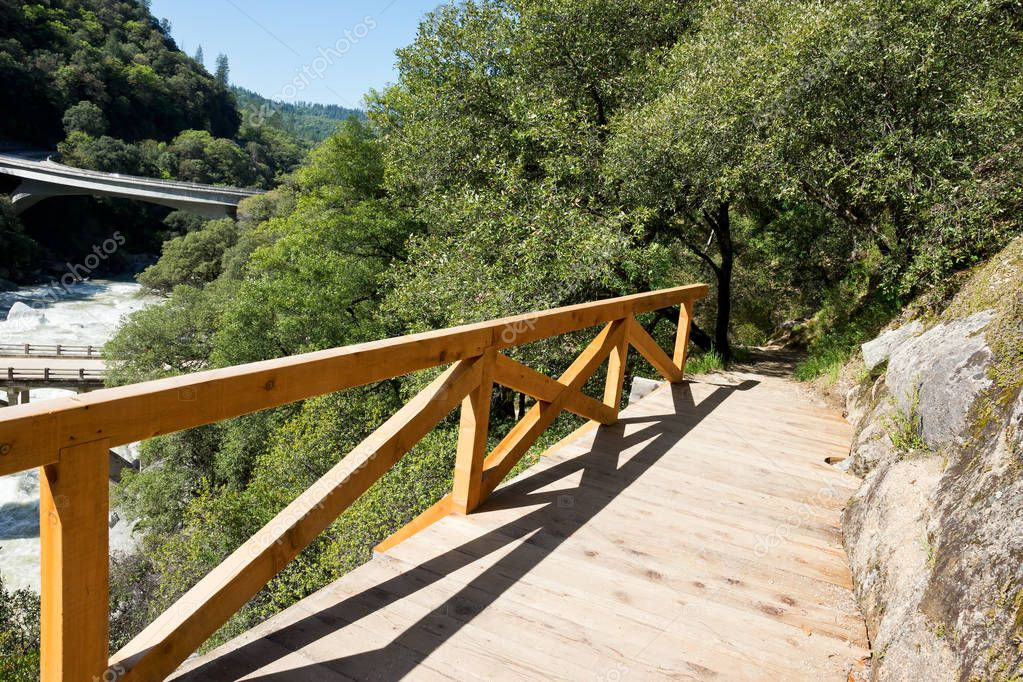 It is early morning near the Hoyt Crossing Trailhead. The Yuba River is seen in the background while on the trail new wood railing is to help prevent from slipping off along the Cliffside.