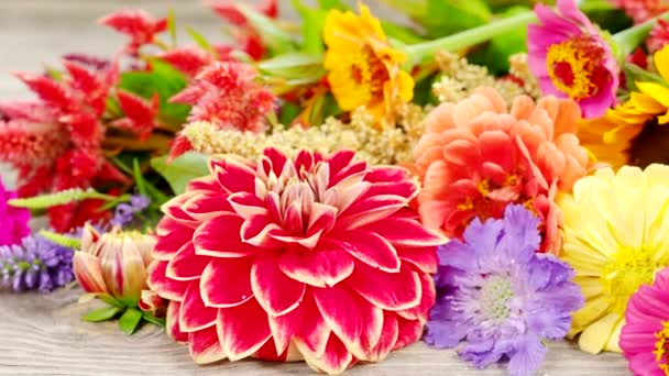Holiday autumn bouquet in 4K VIDEO. Close up of colorful flowers arranged on old wooden background.
