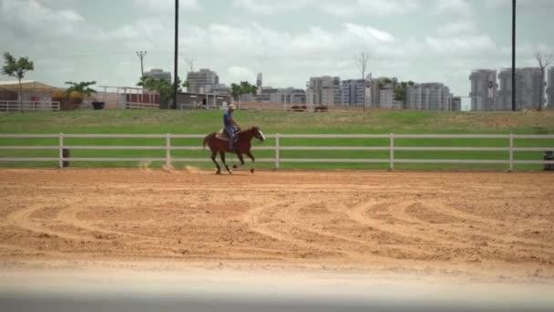 Muž jezdící na koni na farmářských koních. Rančer cvičí pohyby a manévry koní na tréninkové farmě. Koncept zpomaleného západního ranče.