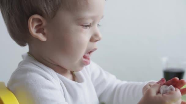 Jeden malý blonďatý chlapec maluje vejce a čisté ruce mokrým ubrouskem.Příprava na Velikonoce. Malování s rukama uvnitř. Tvůrčí vývoj pro děti do 3 let. Vzdělání, kreslení doma během