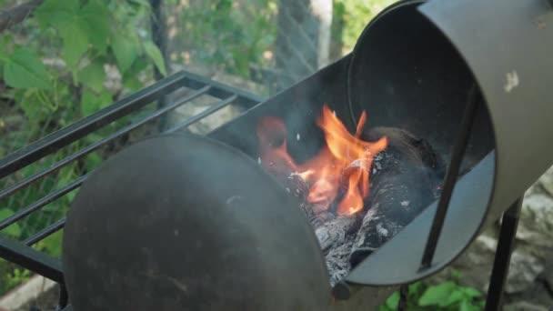 Kochen, orientalische Küche, Waldbrände, Brandschutzkonzept - Anzünden von Feuer und Kohlen in schwarzem Metallgrill zum Räuchern und Braten von Fleisch und Gemüse in der Hitze der Wildtiere im Freien mit Rauch.