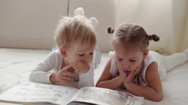 family, innocence, infant concepts - Two smiling children read large interesting book of fairy tales on bed. Siblings little boy and girl brother and sister have fun, happy kids on quarantine at home