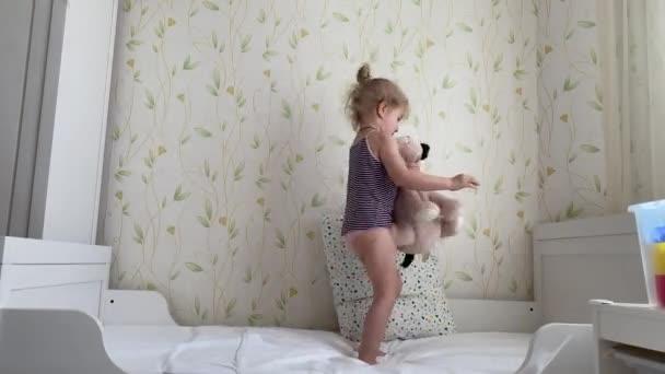 Kis hároméves kislány medvével a karjában ugrál az ágyon és jól érzi magát.