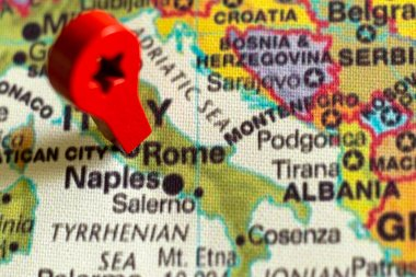 wooden red marker on the map near Rome