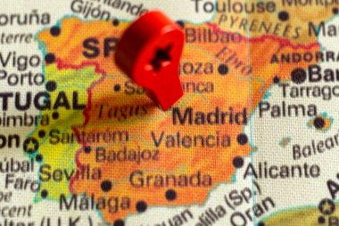 wooden red marker on the map near Madrid