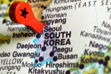 wooden red marker on the map near Seoul