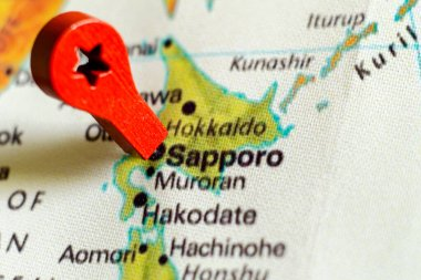 wooden red marker on the map near Sapporo