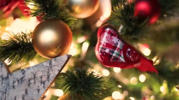 Červený textilní pták visící na vánočním stromě s věnci a zlatými kuličkami