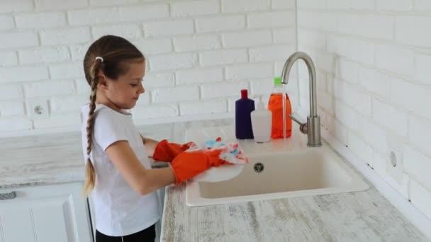 Dívka 7-10 let myje nádobí v kuchyni.