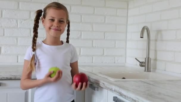Little girl with apples fruit in kitchen. Copy space.