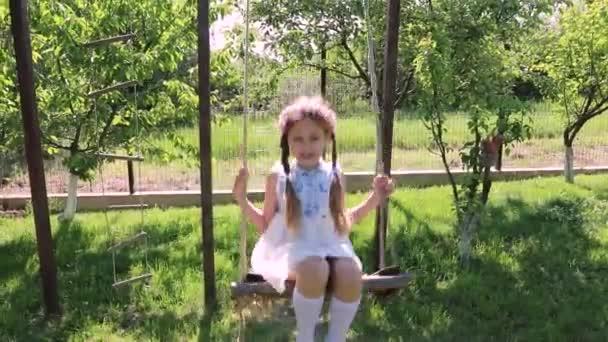 Little girl swinging. little cute girl in a green garden swings on a swing