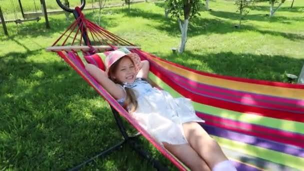 a little girl lying in a hammock on the street in the park. a little sweet girl in a hat lying on a bright hammock. girl in the park, garden