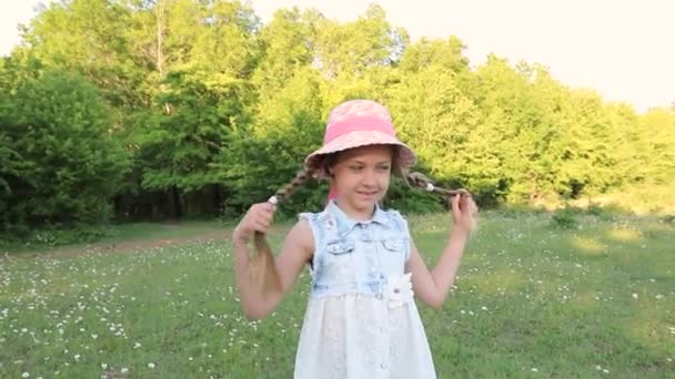 Little cute girl dressed in a dress and a hat laughs in a green summer garden. baby laughter, smile. happiness of the child