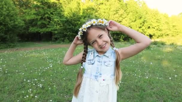 six year old girl with a wreath on her head on the field with chamomiles