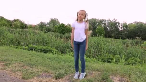 Das Kind in weißem T-Shirt und Jeans springt. kleines Mädchen tanzt in einem grünen Park