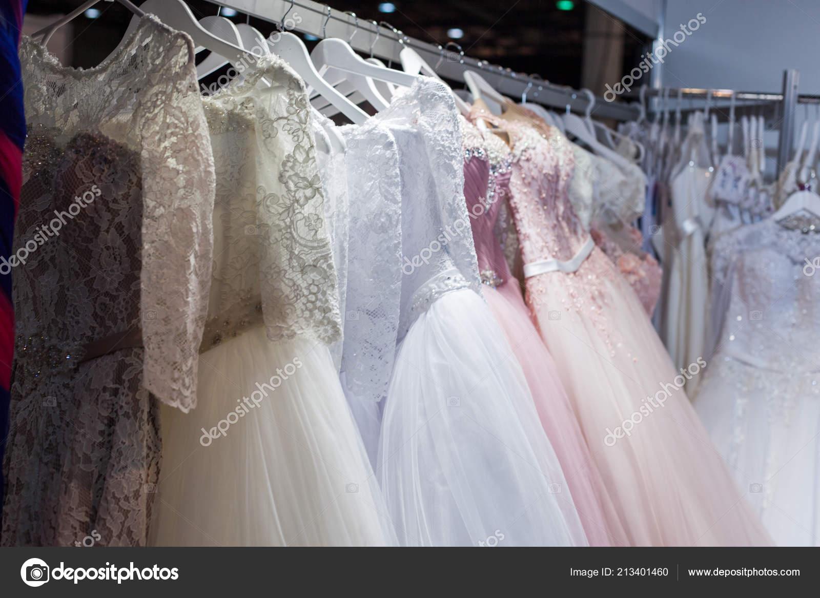 98c80a42aac6 Γάμος και βραδινά φορέματα κρέμεται σε ένα ράφι στο κατάστημα — Εικόνα από  ...