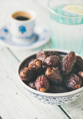 Traditional muslim food for Ramadan iftar meal. Dates, glass of water and coffee over wooden table.