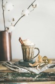 Autumn or Winter hot chocolate or coffee with whipped cream and cinnamon in rustic mug, white background behind