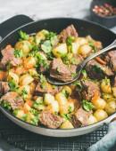 Fleisch essen. Geschmortes Rindfleisch mit Kartoffeln und Karotten mit Petersilie in Kochen Pfanne über weißen Marmor Tabellenhintergrund, Tiefenschärfe, vertikale Zusammensetzung. Winter-Hausmannskost