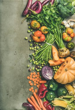 Healthy vegetarian seasonal Fall food cooking background. Flat-lay of Autumn vegetables and herb from local market over grey concrete background, top view, copy space. Clean eating, alkaline diet food