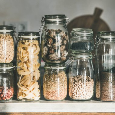 Kitchen food storage arrangement. Grains, cereals, nuts, dry fruit, flour, pasta kinds in glass jars over concrete kitchen counter, square crop. Clean eating, healthy, vegan, balanced diet concept