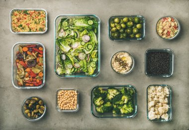 Healthy vegan dishes in containers. Flat-lay of vegetable salads, legumes, beans, fermented olives, sprouts, hummus dip, couscous for take-away lunch, top view. Spring menu, clean eating, dieting food