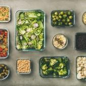 Fotografie Zdravé veganské pokrmy v kontejnerech. Ploché a zeleninové saláty, luskoviny, fazole, fermentované olivy, kapusty, homos DIP, kuskus pro polední oběd, vrcholový výhled, hranatá úroda. Jarní menu, čisté stravování