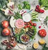 Vegetáriánus snack-tábla. Lapos, cékla hummus, joghurt dip, kinoa saláta, olajbogyó, beens, zöldségek és gyümölcsök Flatbread mint szürke beton háttér, felülnézet. Vegeratiánus párt élelmiszer koncepció