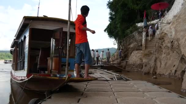 Longtail csónak és turisták sétálnak fel a Pak Ou barlangok, Laosz